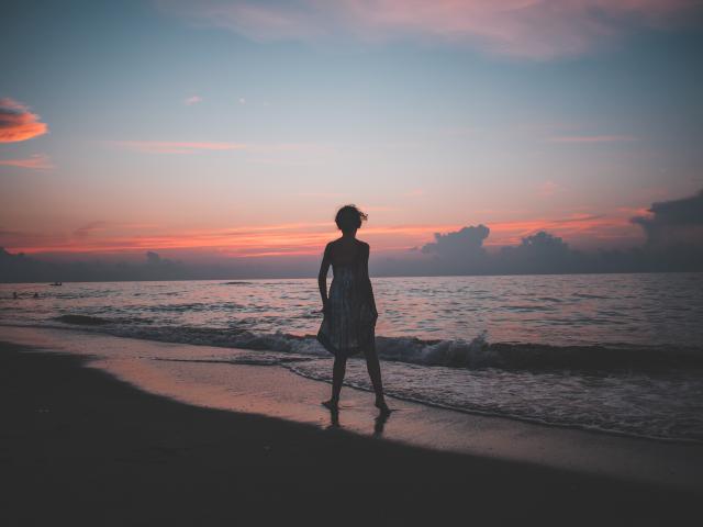 Dame regardant le coucher de soleil sur la plage